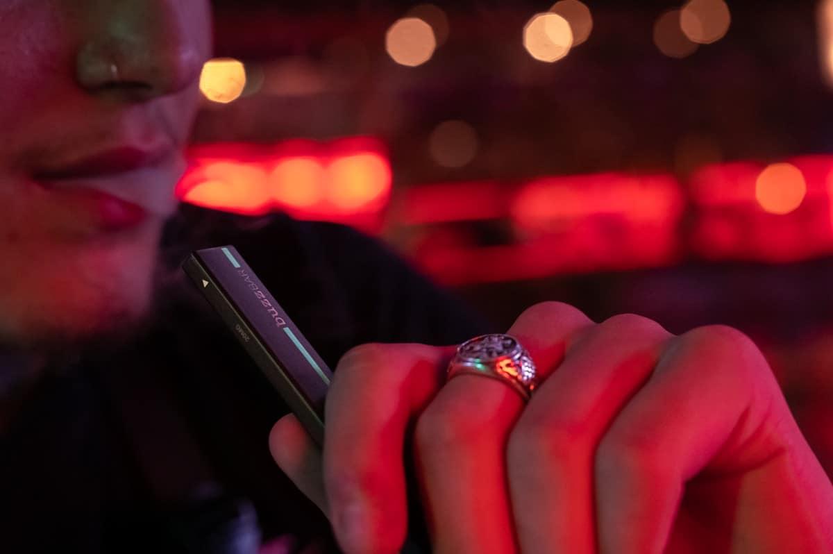 Man taking a drag from a Buzz Bar Menthol Disposable Vape at night