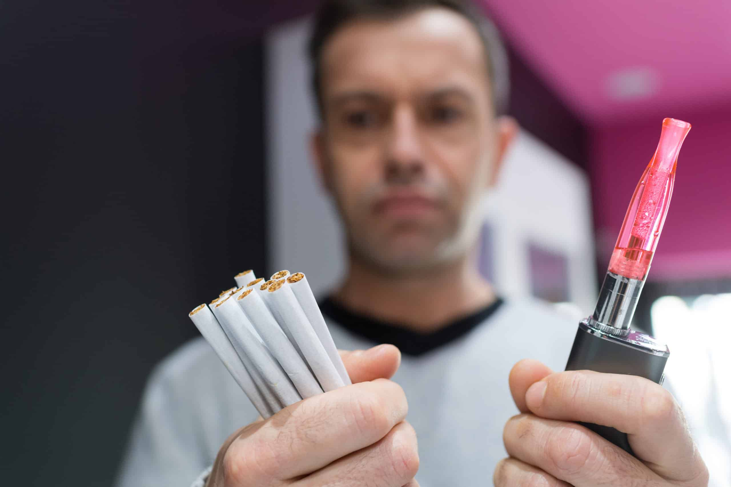 Adult man chooses between cigarettes and vape device.